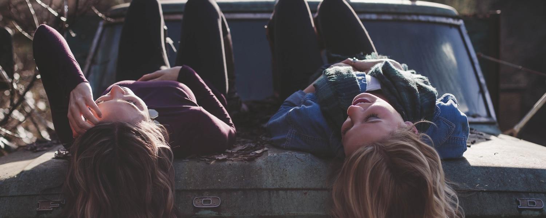 Dos chicas acostadas de espalda sonriendo