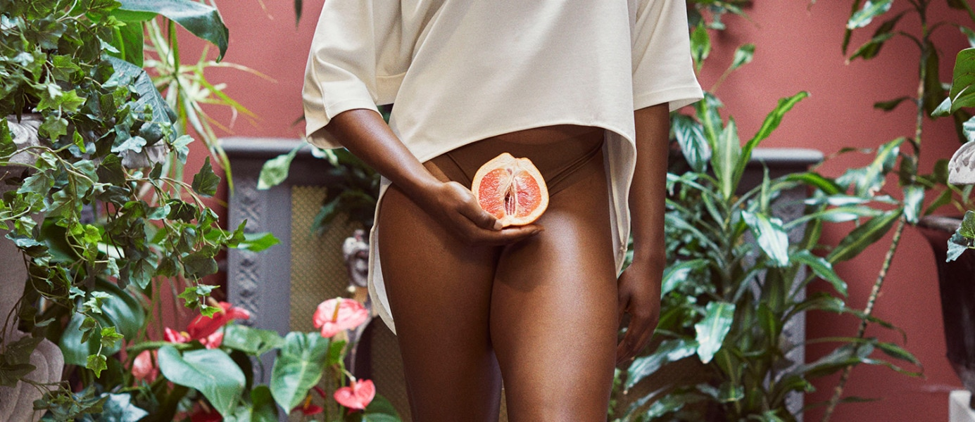 Photo of a woman in a blouse and underwear, holding half a grapefruit in front of her panties - Libresse