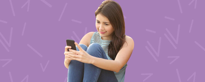 Imagen de una niña leyendo en su teléfono celular sobre un fondo morado - Saba