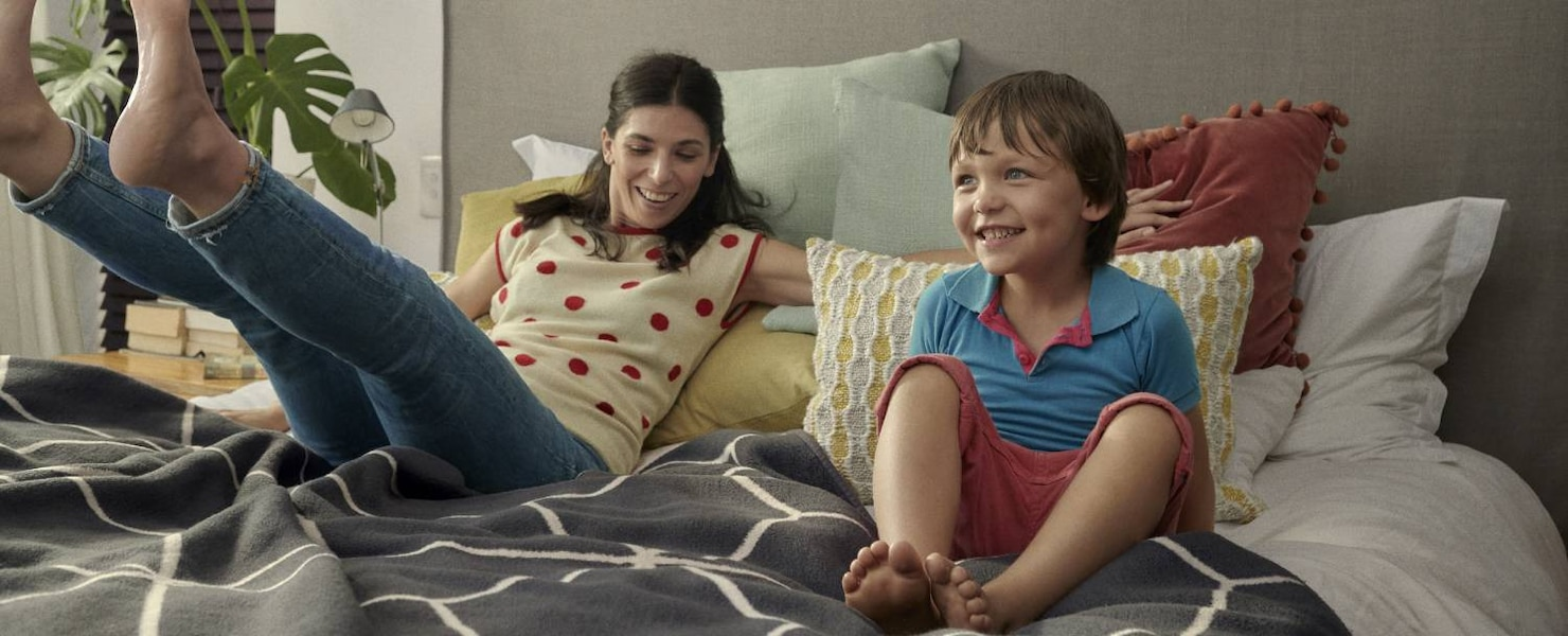 Woman sitting on her bed with a young children