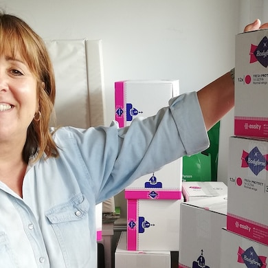 Woman in front of boxes of Bodyform sanitary products