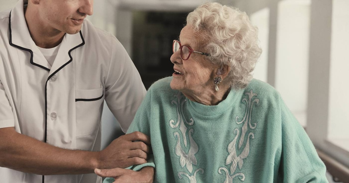 Elderly woman walking with her carer
